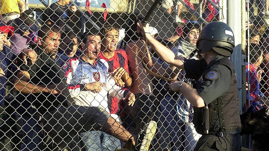 Torcedores do San Lorenzo tentam quebrar a grade que separa a arquibancada do campo ao serem reprimidos por um policial, em partida contra o Independiente