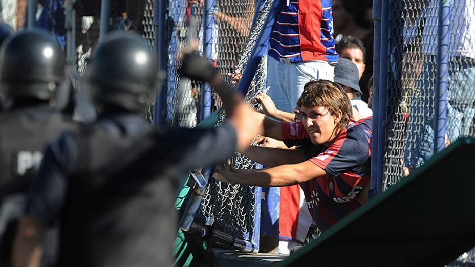Policiais tentam controlar torcedores do San Lorenzo durante confusão nas arquibancadas do estádio José Amalfitani, em Buenos Aires