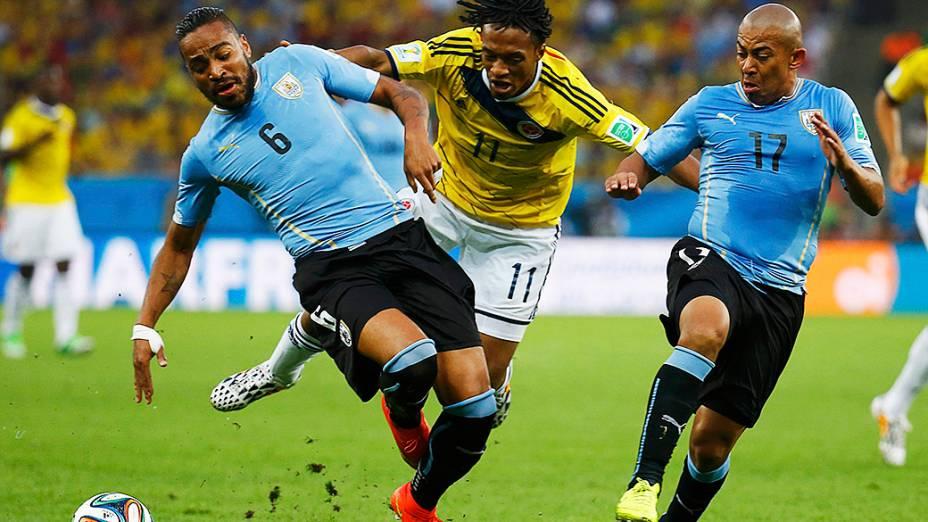Jogadores de Colômbia e Uruguai disputam a bola durante as oitavas de final no Maracanã, no Rio