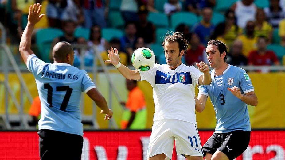 Da Itália, Alberto Gilardino controla a bola entre o Uruguai Diego Godin e Egidio Arevalo durante a Copa das Confederações terceiro lugar na Arena Fonte Nova, em Salvador