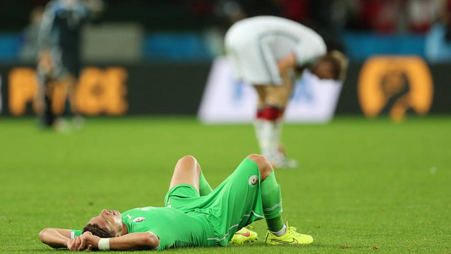 Jogador da Argélia cai em campo exausto, no segundo tempo da prorrogação durante o jogo contra a Alemanha no Beira-Rio, em Porto Alegre