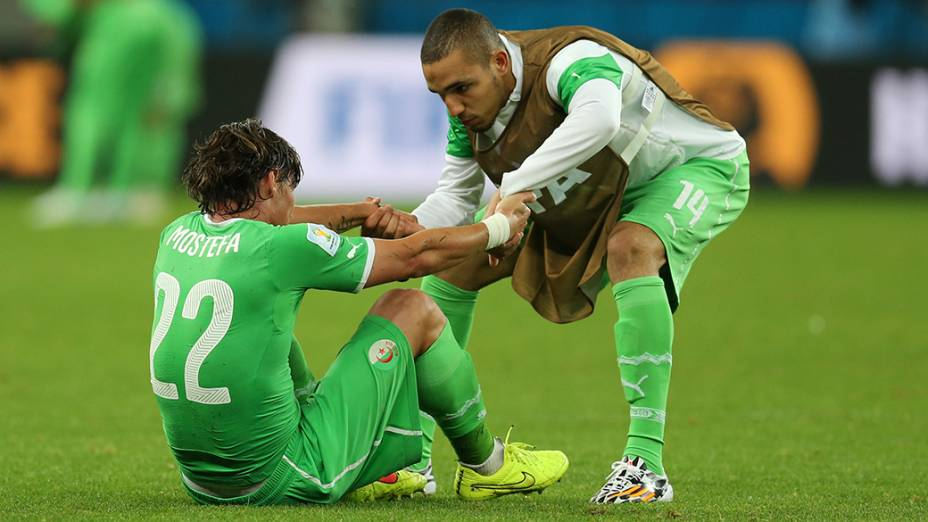 Jogador da Argélia ajuda seu companheiro após a derrota para a Alemanha no Beira-Rio, em Porto Alegre