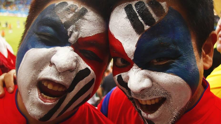 Torcedores pintam a bandeira da Coreia do Sul no rosto parapartida contra a Rússia na Arena Pantanal, em Cuiabá