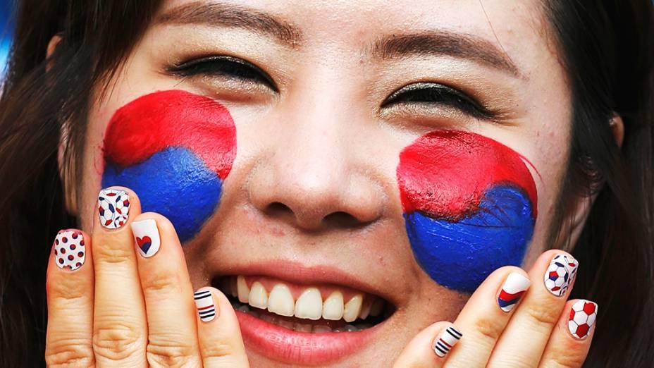 Torcedora pinta a bandeira da Coreia do Sul no rosto parapartida contra a Rússia na Arena Pantanal, em Cuiabá
