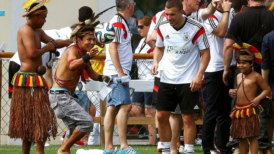 O jogador Lukas Podolski olha um índio brincando com a bola