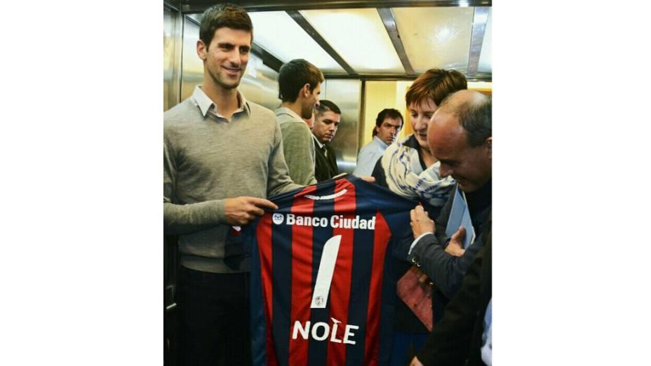 Novak Djokovic recebe a camisa do time argentino Clube Atlético San Lorenzo durante visita a uma escola estadual na cidade de Buenos Aires
