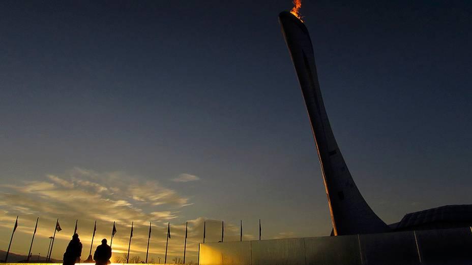 Agentes de segurança, passam pela pira olímpica durante o nascer do sol no Parque Olímpico de Sochi