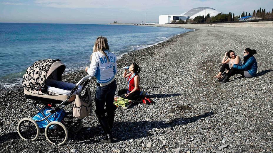 Moradores aproveitam o bom tempo para ir à praia, no Mar Negro, nas proximidades do Parque Olímpico em Sochi, durante os Jogos de Inverno