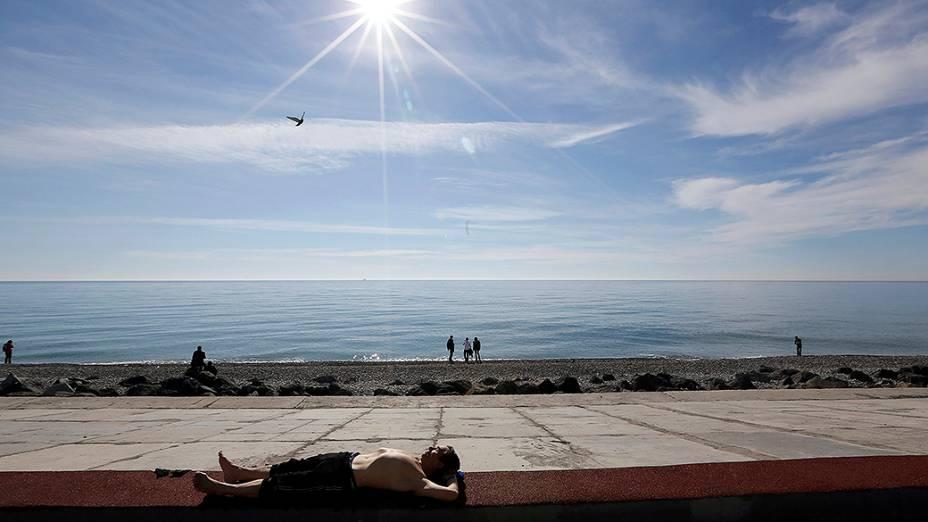 Homem toma banho de sol nas proximidades do Parque Olímpico em Sochi, durante os Jogos de Inverno
