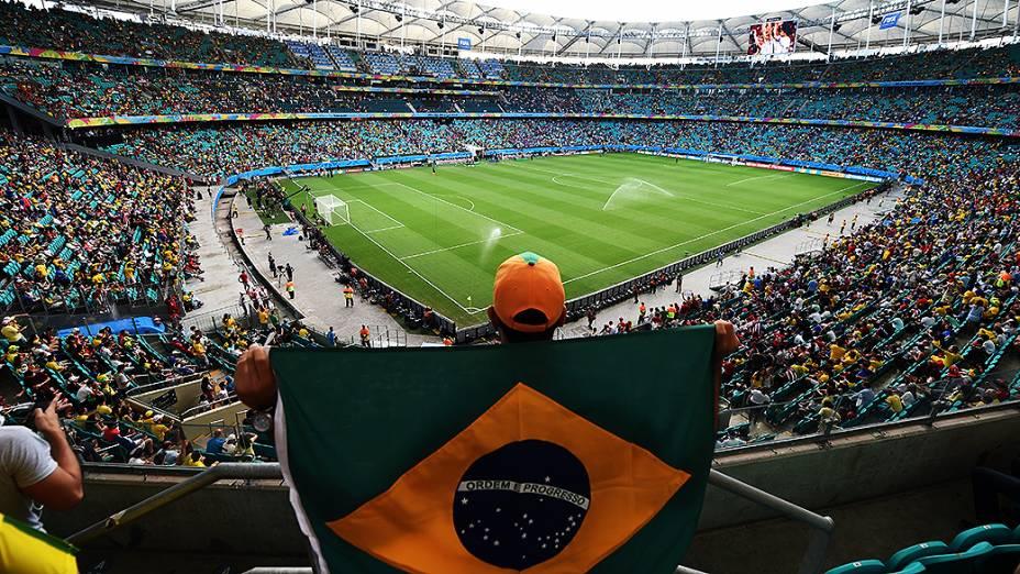 Torcedor segura bandeira do Brasil antes do jogo entre Bélgica e Estados Unidos na Arena Fonte Nova, em Salvador