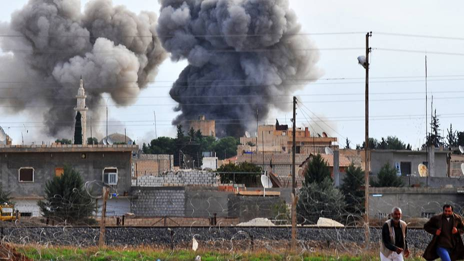 Pessoas correm após bombardeio aéreo sírio na cidade fronteiriça Ras al-Ain, na Turquia