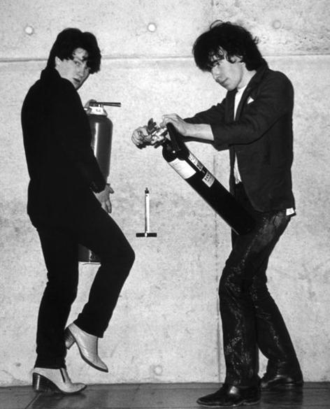 Bono Vox e The Edge brincam com extintores de incêndio durante sessão de fotos na Universidade de Trinity em Dublin, em fevereiro de 1979