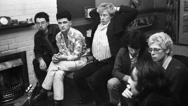 """Dik Evans, Gavin Friday e Guggi acompanham The Edge e Adam Clayton durante entrevista com Bill Graham (em primeiro plano) da revista """"Phyl Clarke"""", em fevereiro de 1979"""