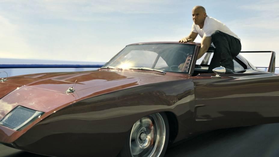 Não satisfeito em ficar sentado ao volante de seu Daytona 1969, Toretto faz pose pendurado na porta do carro