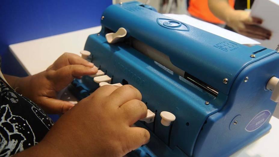 Pessoa com deficiência visual digita em máquina de escrever que utiliza o método Braille