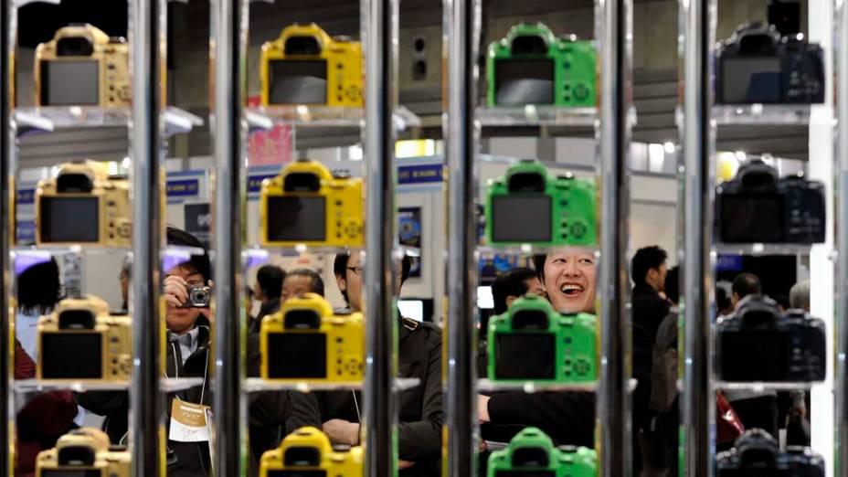 Pessoas observam câmeras fotográficas durante feira de fotografia em Tóquio