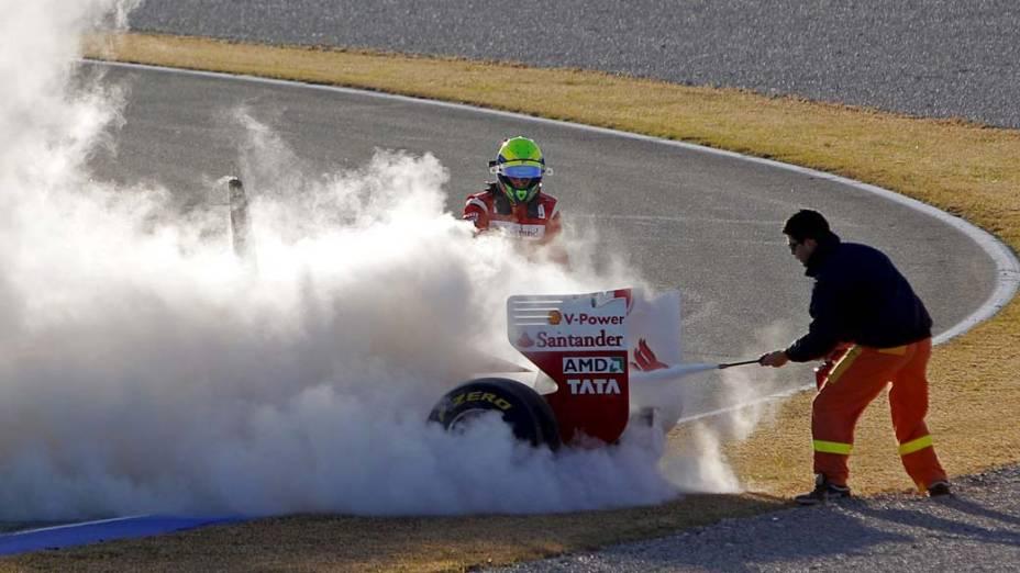 Felipe Massa da Ferrari observa o carro que pegou fogo durante os treinos para a Fórmula 1 em Valencia, Espanha