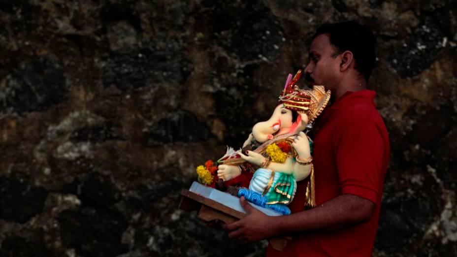 Indiano carrega imagem do deus Ganesha durante as festividades do Ganesh Chaturthi, que celebra o nascimento do deus
