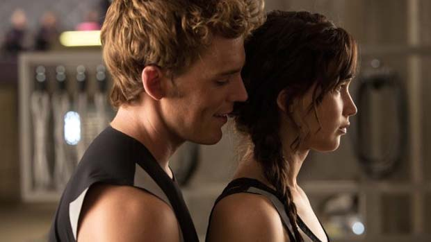 Sam Claflin e Jennifer Lawrence no filme Jogos Vorazes: Em Chamas