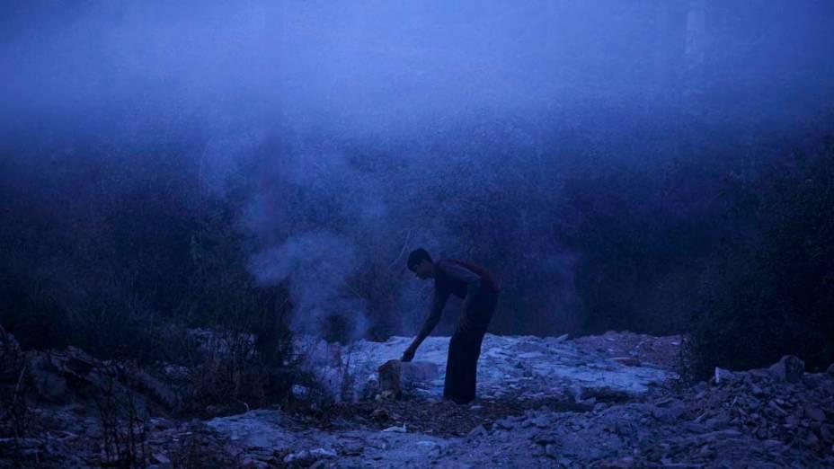 Homem acende fogueira para se aquecer em Nova Délhi, Índia