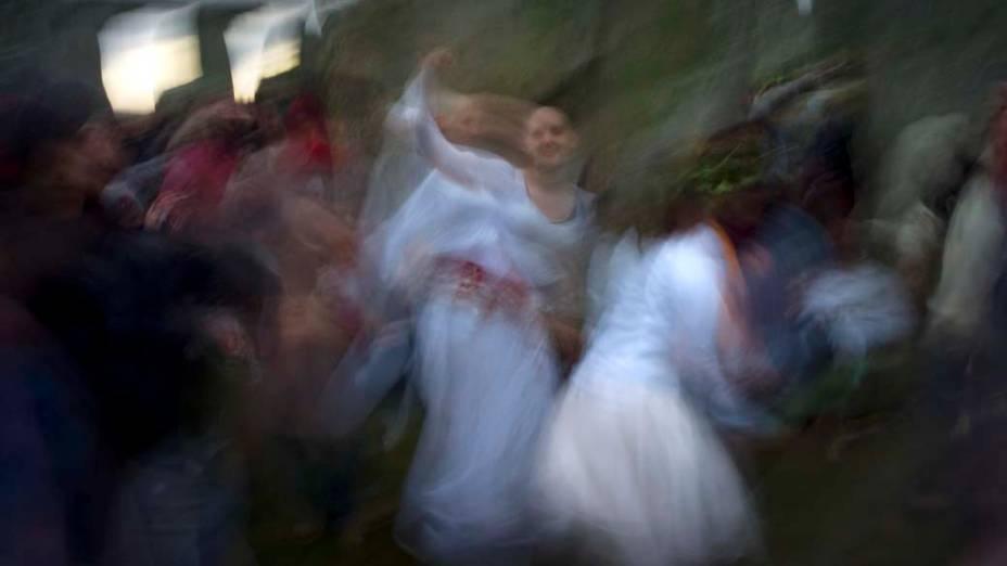 Foliões dançam ao nascer do sol no solstício de inverno, dia mais curto do ano, no Stonehenge em Salisbury, Reino Unido
