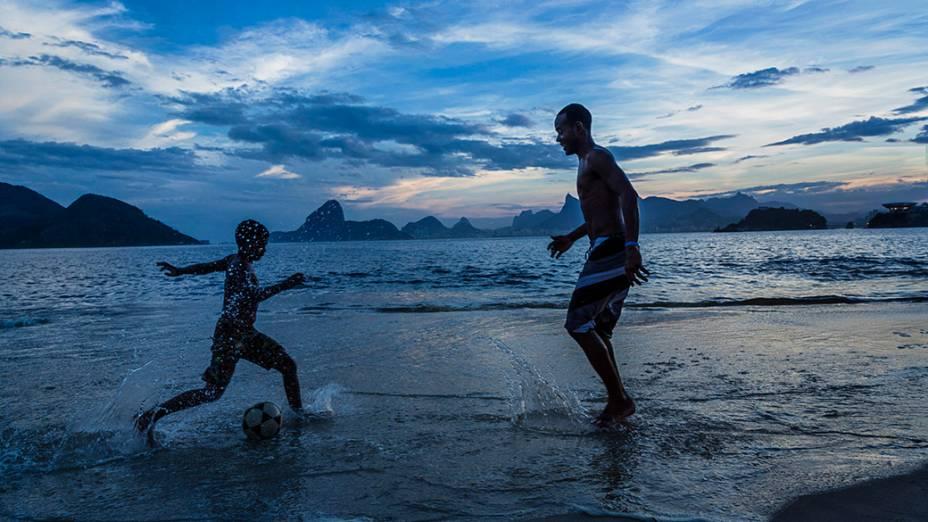 Pai e filho jogam futebol na praia de Niterói, no Rio de Janeiro ao entardecer