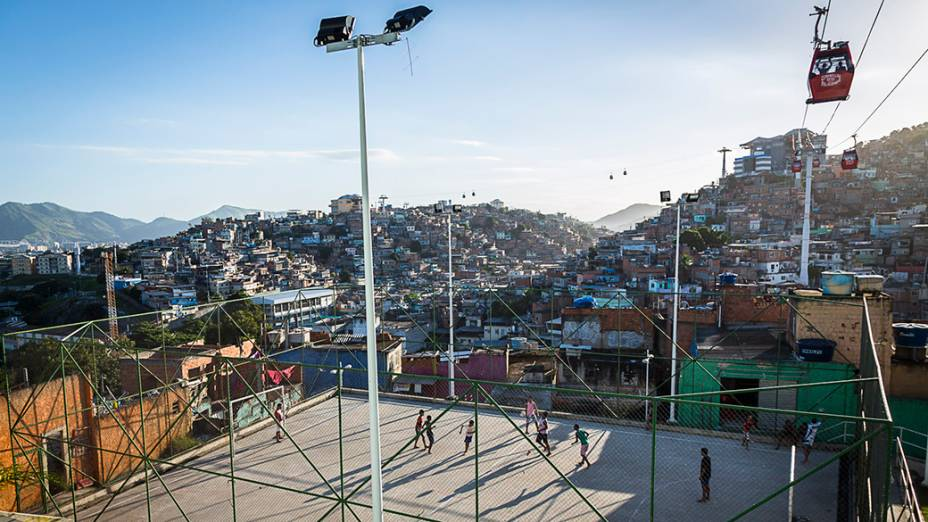 Partida de futebol disputada na quadra de uma comunidade enquanto o teleférico transporta moradores no Complexo do Alemão, no Rio de Janeiro