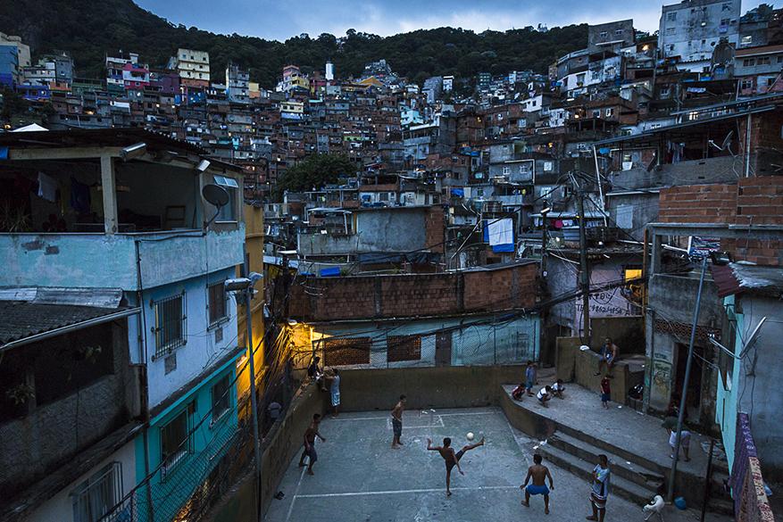 Jovens jogam futebol no coração da favela da Rocinha, considerada a mais densamente povoada do Rio de Janeiro
