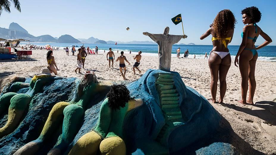 Um grupo de amigos joga futebol na praia de Copacabana próximo a uma escultura de areia representando cariocas tomando banho de sol, sob o olhar atento do Cristo Redentor - Rio de Janeiro, 2013