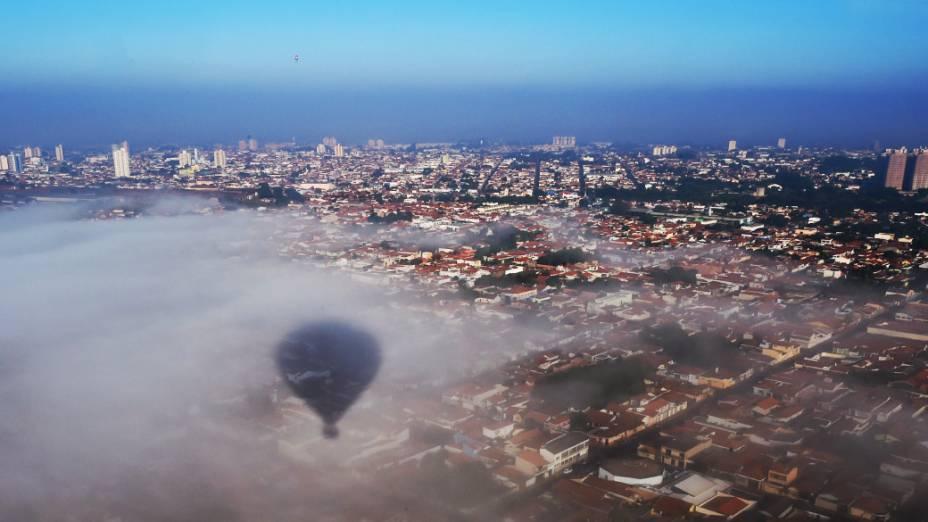 Sombra de um balão é projetada em nuvem sobre a cidade de Rio Claro, no interior paulista