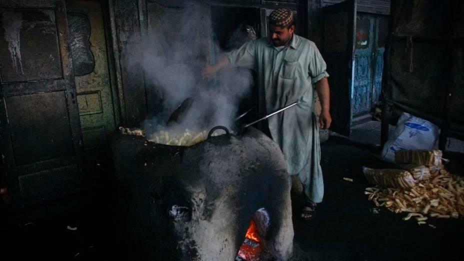 Homem frita biscoitos em loja na cidade de Quetta, Paquistão