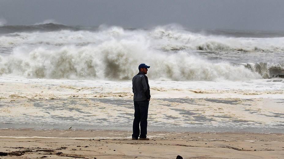 Homem olha para a costa enquanto as ondas provocadas pela passagem do Sandy se aproximam. Bolsa de Nova York fecha por causa de furacão Sandy