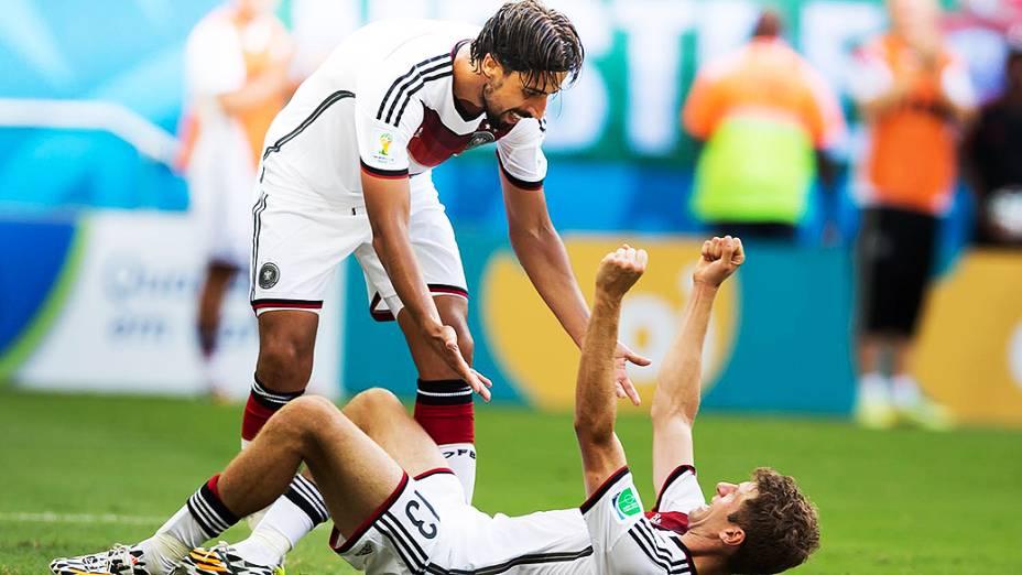 O alemão Sami Khedira ajuda seu companheiro Thomas Müller a se levantar