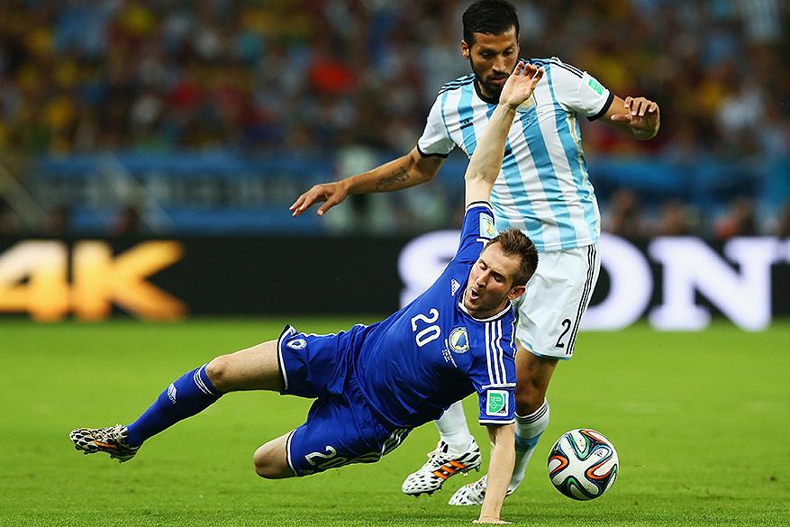 Izet Hajrovic, da Bósnia, disputa a bola com o argentino Garay no Maracanã, no Rio