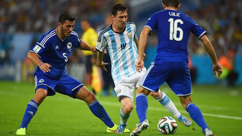 O argentino Lionel Messi dribla dois jogadores da Bósnia no Maracanã, no Rio