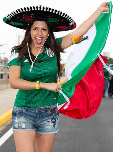Torcedora do México segura bandeira do país antes do jogo contra o Brasil no Castelão, em Fortaleza