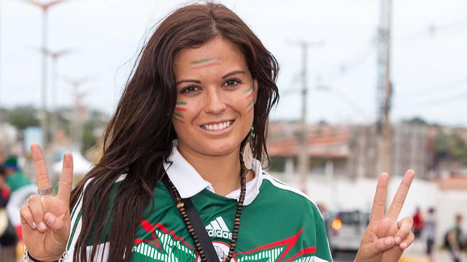 Torcedora pinta o rosto com as cores da bandeira do México antes do jogo contra o Brasil no Castelão, em Fortaleza