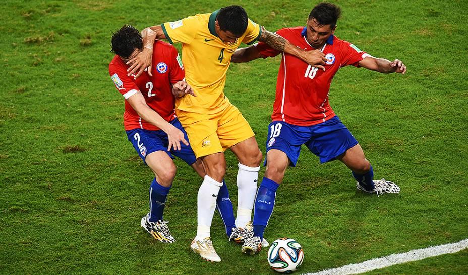 Tim Cahill, da Austrália, disputa a bola com dois jogadores do Chile, na Arena Pantanal em Cuiabá