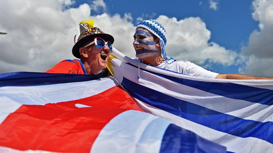 Torcedores seguram as bandeiras da Costa Rica e do Uruguai, no Castelão em Fortaleza