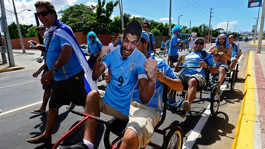 Grupo de torcedores do Uruguai chegam no Castelão de triciclos com a imagem de Luis Suárez na frente, em Fortaleza