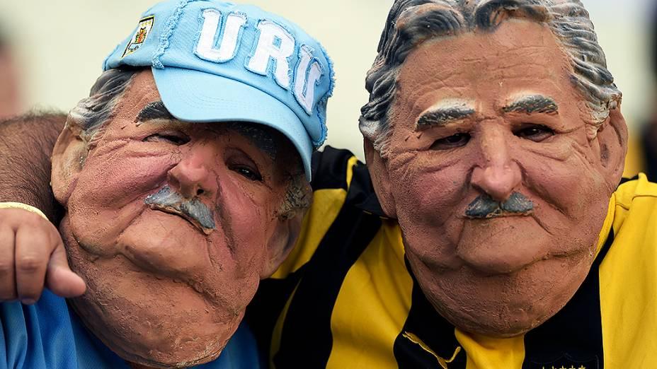 Torcedores do Uruguai usam máscara do presidente José Mujica antes do jogo contra a Costa Rica, no Castelão em Fortaleza