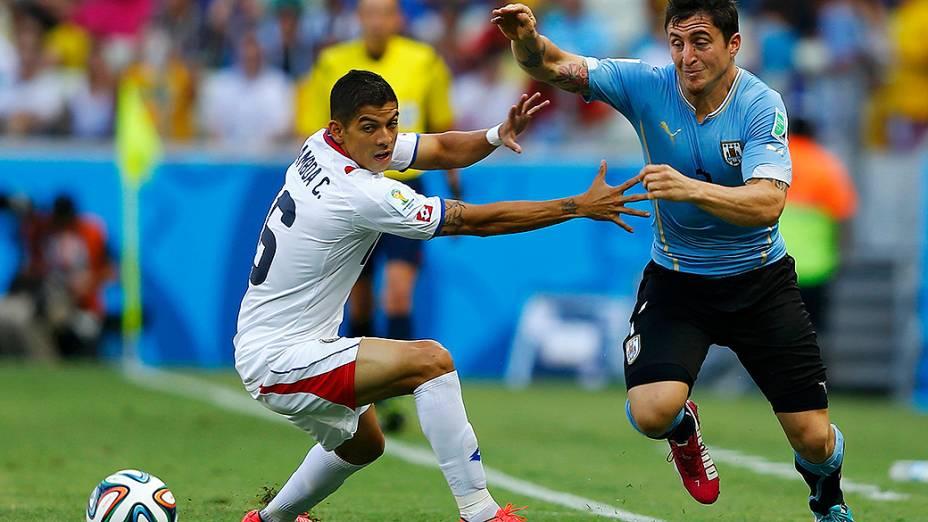 Cristian Gamboa, da Costa Rica, disputa a bola com o uruguaio Cristian Rodriguez, no Castelão em Fortaleza