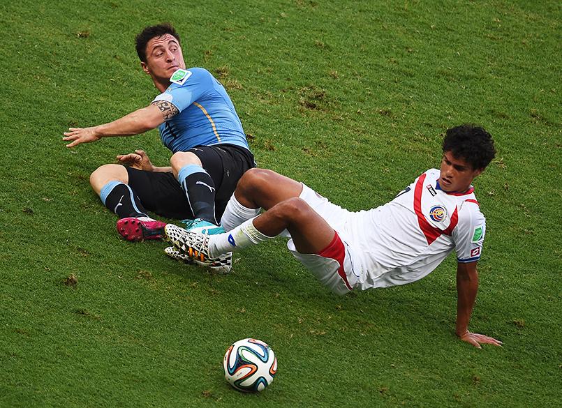 Cristian Rodriguez, do Uruguai, disputa a bola com Yeltsin Tejeda, da Costa Rica, em Fortaleza