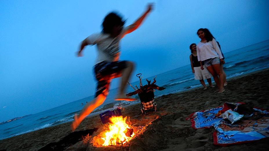 Homem salta sobre uma fogueira durante as celebrações de São João em uma praia de Alicante, na Espanha