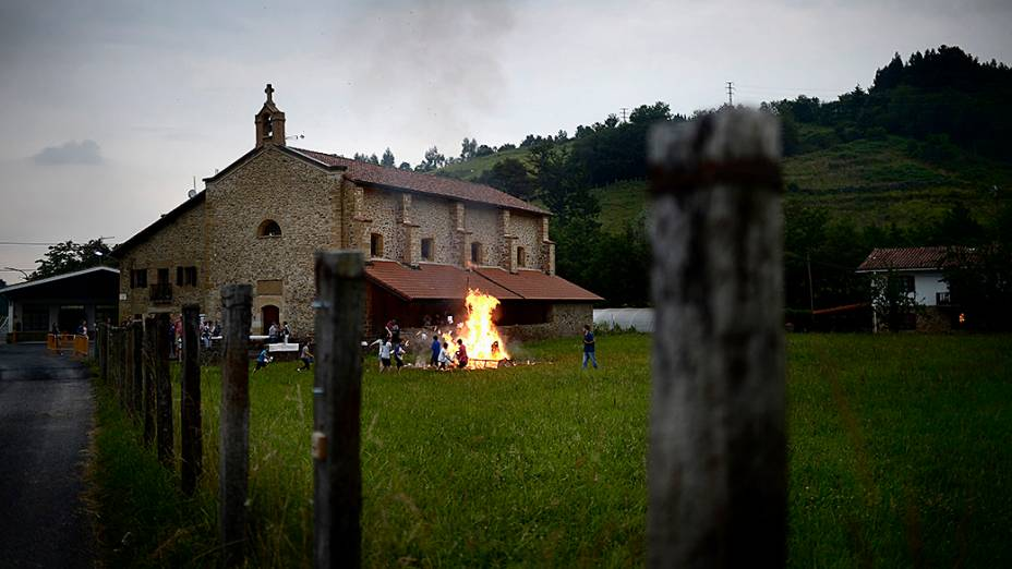 Crianças jogam livros didáticos antigos em uma fogueira durante as celebrações de São João, em Mugica. Na Espanha, é costume queimar objetos antigos na noite de São João como forma de purificar e queimar os problemas para o resto do ano