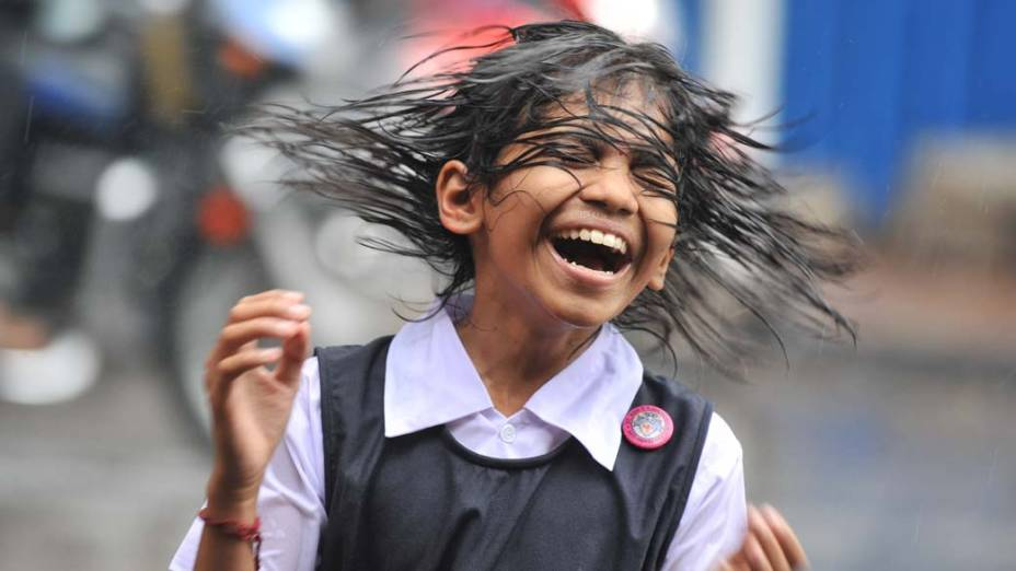 Garota indiana brinca na chuva em Hyderabad