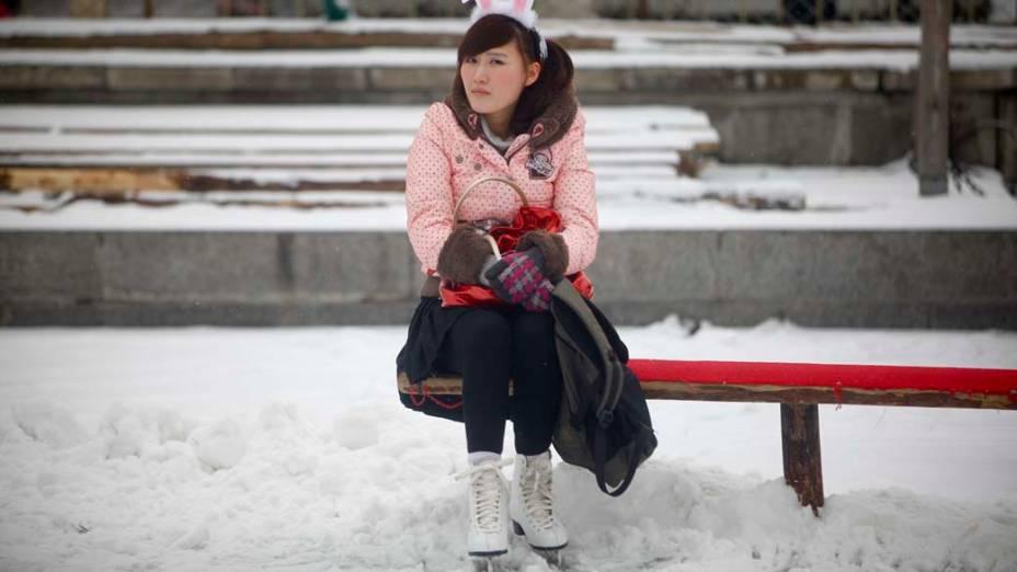 Garota chinesa descansa sobre um lago congelado em Pequim