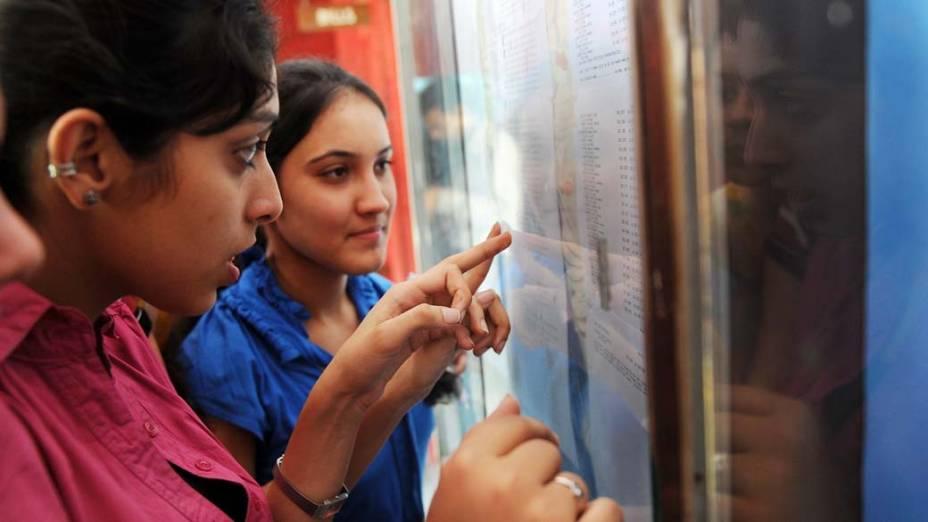 Estudantes indianas conferem resultado de provas em colégio na cidade de Nova Délhi