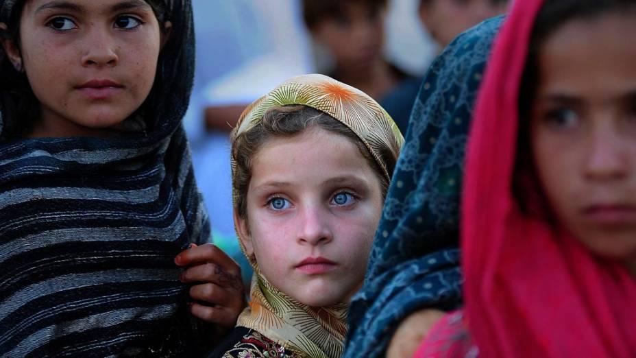 Crianças de famílias que fugiram de suas casas, temendo ataques violentos entre o exército e militantes islâmicos, aguardam em fila por distribuição de alimentos em Jalozai, no Paquistão