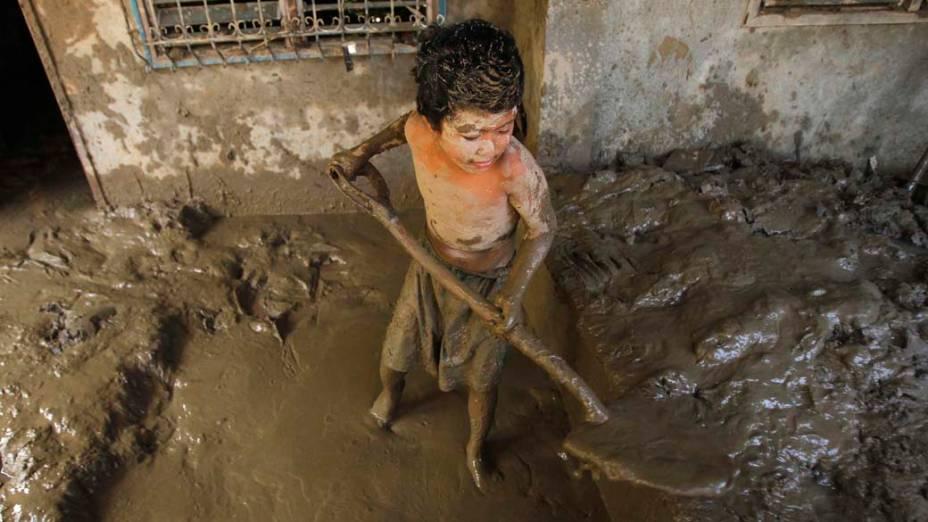 Gartoto limpa lama de sua casa afetada pelas enchentes na cidade de Iligan, Filipinas